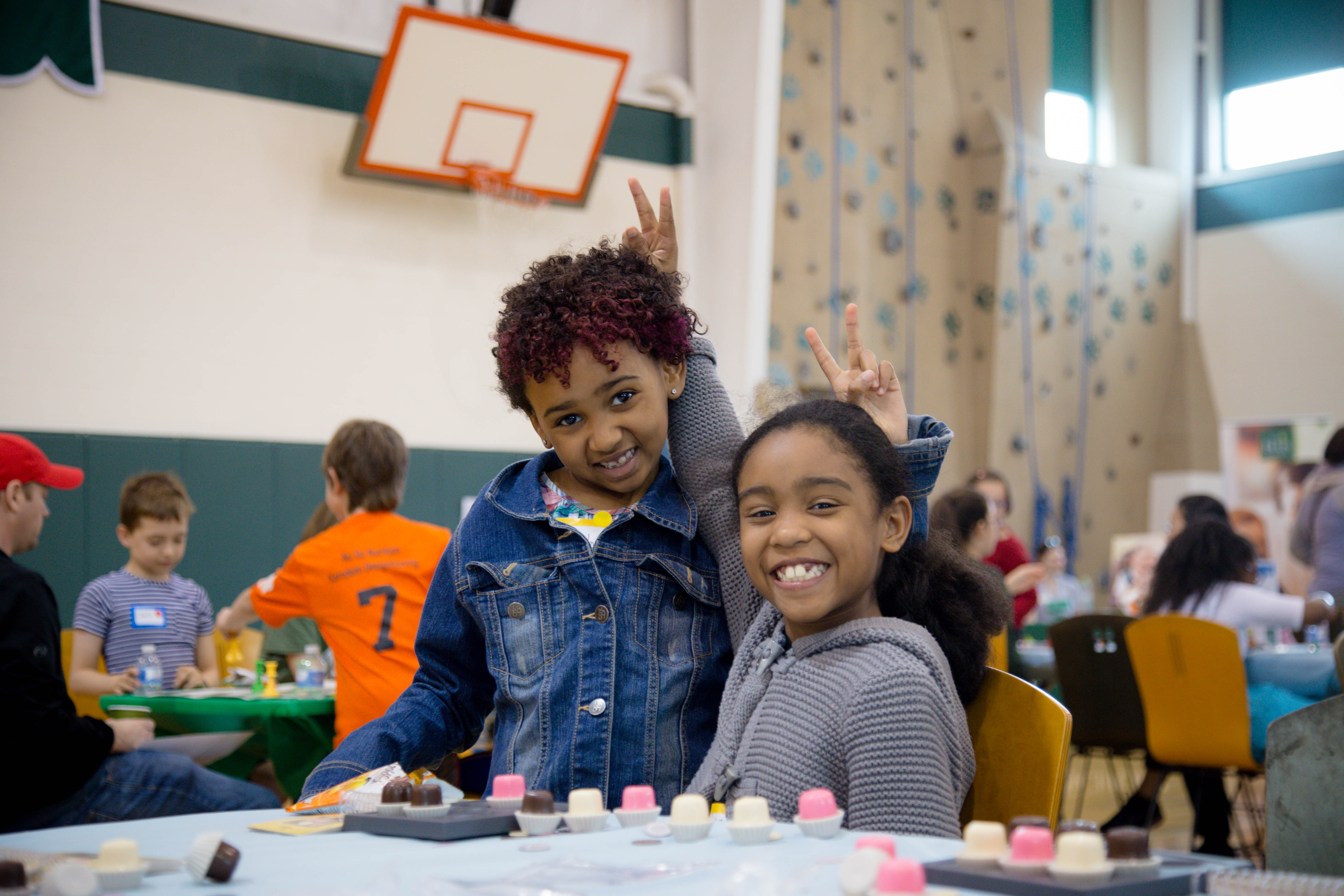 This is a photo of two girls smiling and posing together at the Julia Robinson Mathematics Festival at The Ellis School.